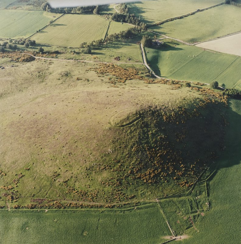 Oblique aerial view centred on the remains of the fort with the remains of the cottage, huts and sheepfold adjacent, taken from the SSW.