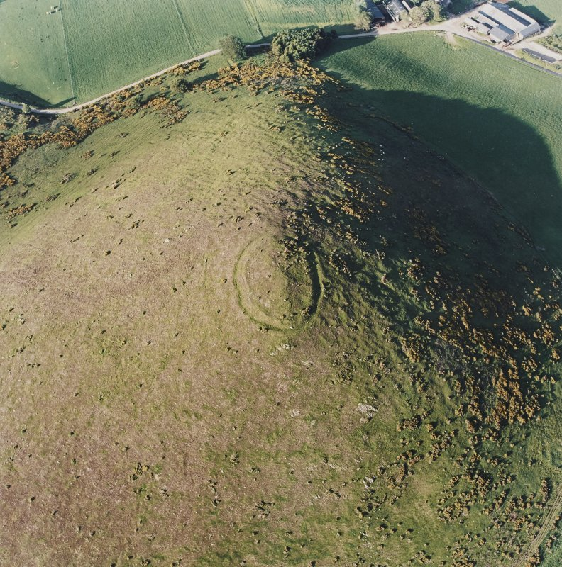 Oblique aerial view centred on the remains of the fort with the remains of the cottage, huts and sheepfold adjacent, taken from the SW.