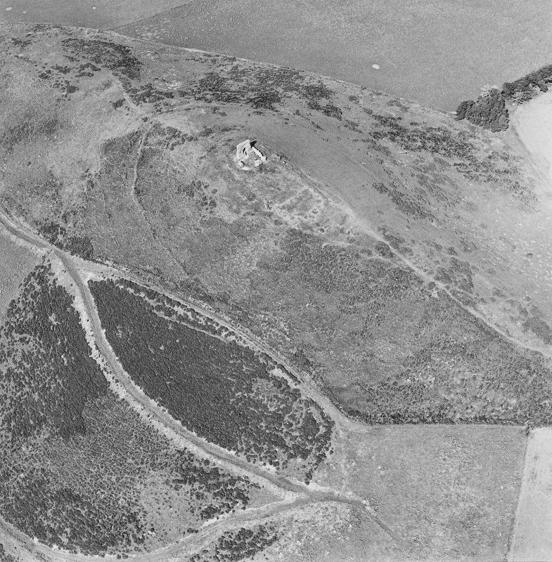 Oblique aerial view of Dunnideer centred on the remains of a fort and tower-house, taken from the SE.