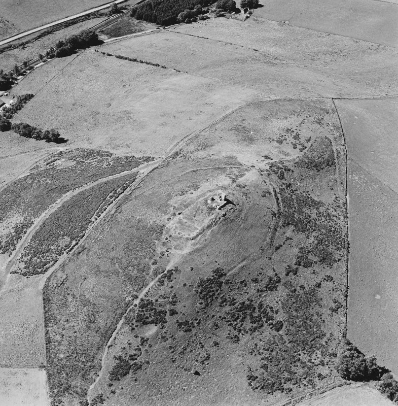 Oblique aerial view of Dunnideer centred on the remains of a fort and tower-house, taken from the ENE.