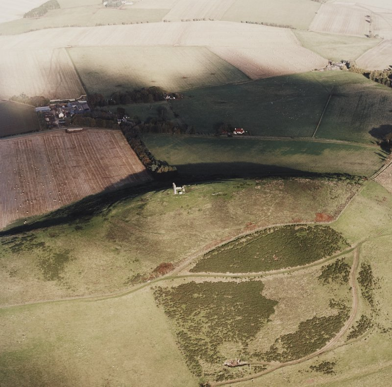 Oblique aerial view of Dunnideer centred on the remains of the fort and tower-house, taken from the SW.