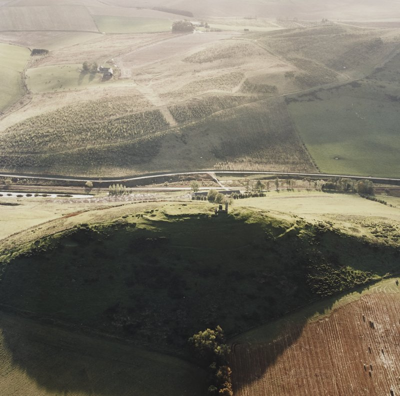 Oblique aerial view of Dunnideer centred on the remains of the fort and tower-house, taken from the NE.