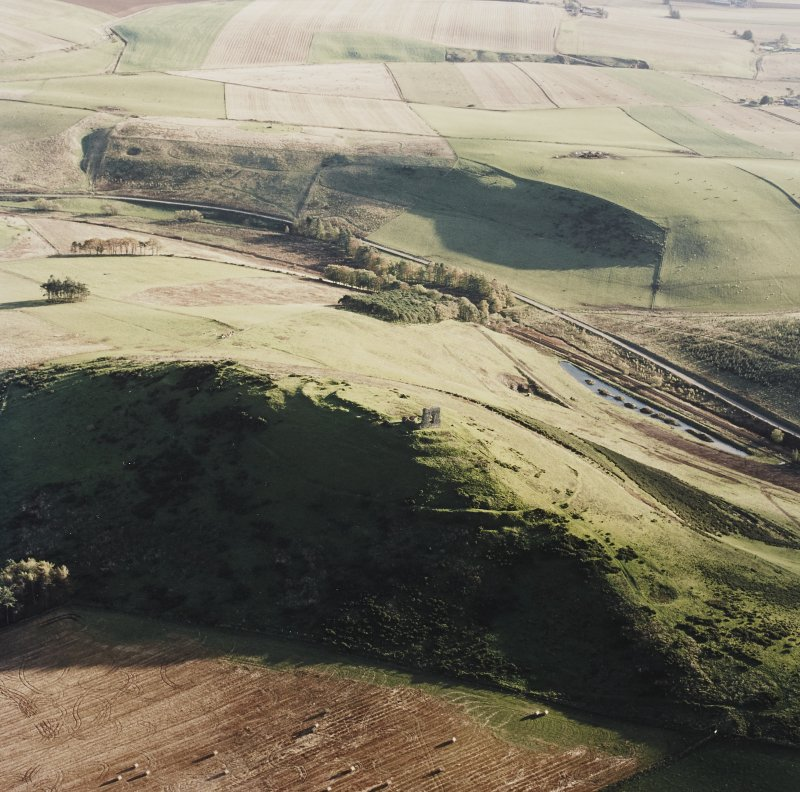 Oblique aerial view of Dunnideer centred on the remains of the fort and tower-house, taken from the N.