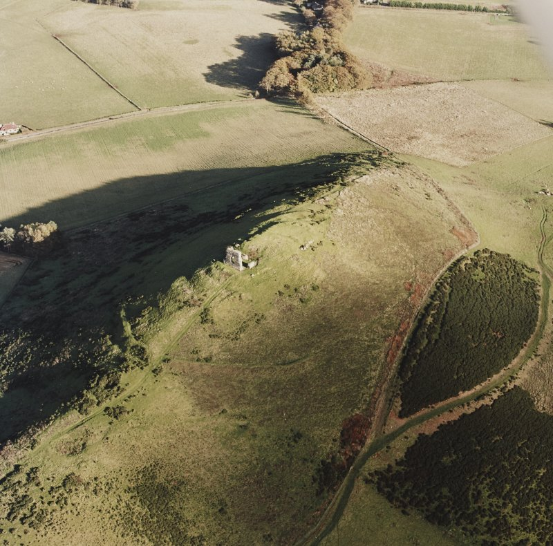 Oblique aerial view of Dunnideer centred on the remains of the fort and tower-house, taken from the W.