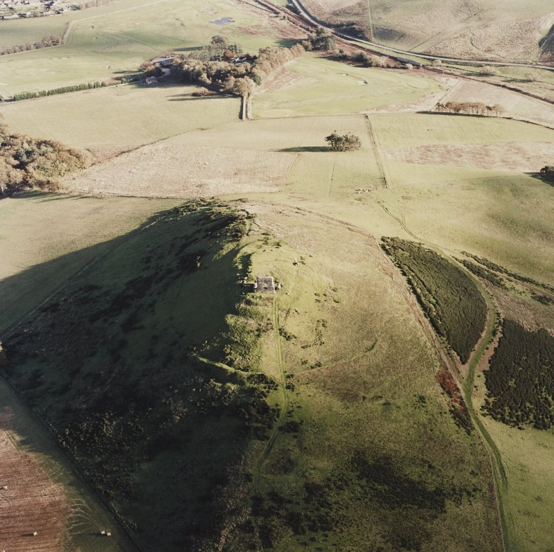 Oblique aerial view of Dunnideer centred on the remains of the fort and tower-house, taken from the NW.