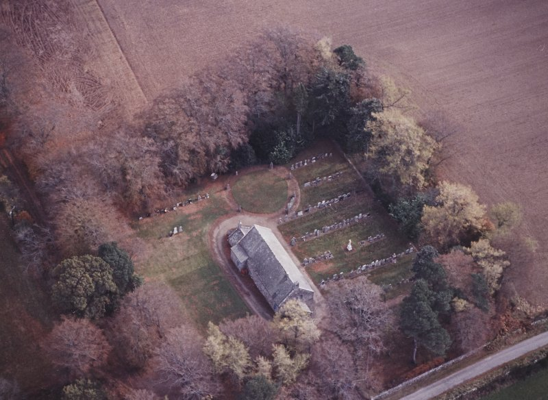 Oblique aerial view centred on the remains of the recumbent stone circle, the church and burial-ground, taken from the WNW.
