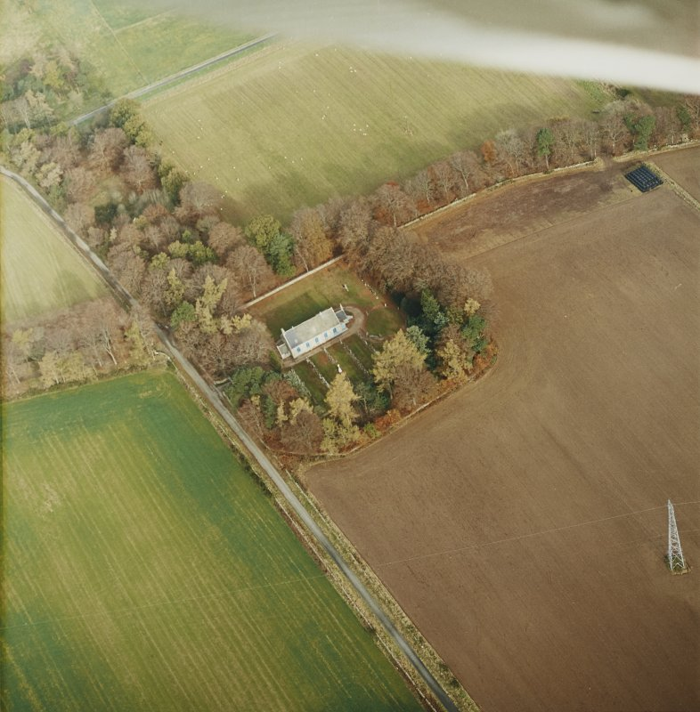Oblique aerial view centred on the remains of the recumbent stone circle, the church and burial-ground, taken from the SW.