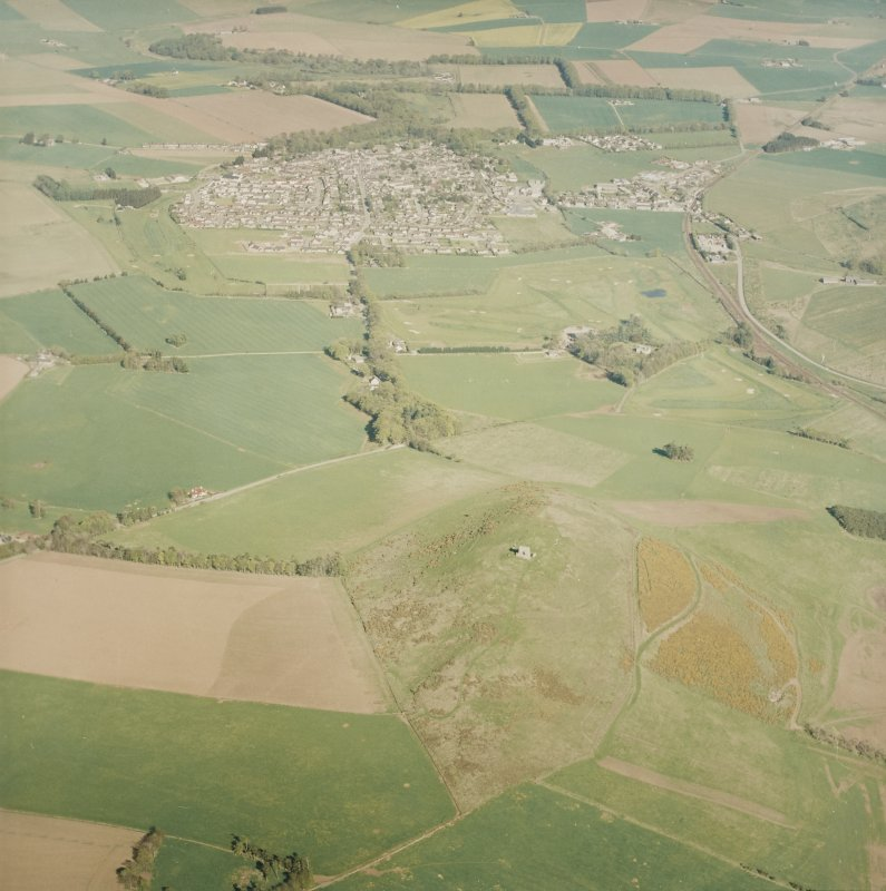 Oblique aerial view centred on the remains of the fort with village adjacent, taken from the W.