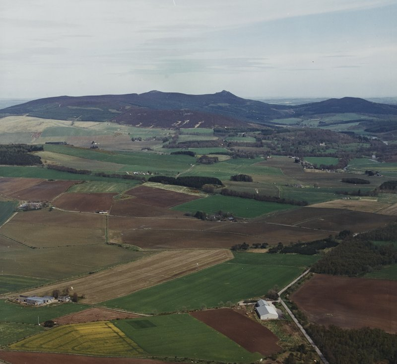 General oblique aerial view looking across the farmsteadings and cottages towards Bennachie and the remains of the fort, taken from the WSW.