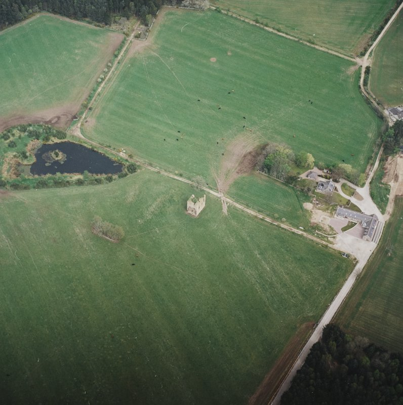 Oblique aerial view centred on the ruins of the tower-house with the farmsteading adjacent, taken from the SW.