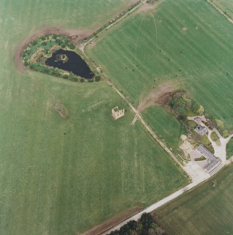Oblique aerial view centred on the ruins of the tower-house with the farmsteading adjacent, taken from the S.