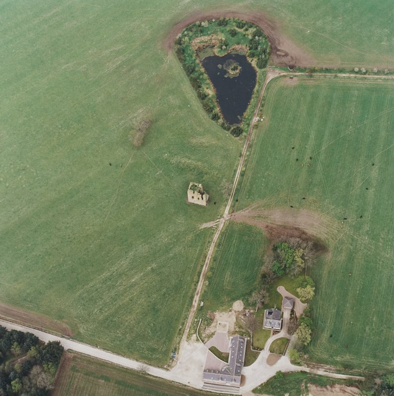 Oblique aerial view centred on the ruins of the tower-house with the farmsteading adjacent, taken from the SE.