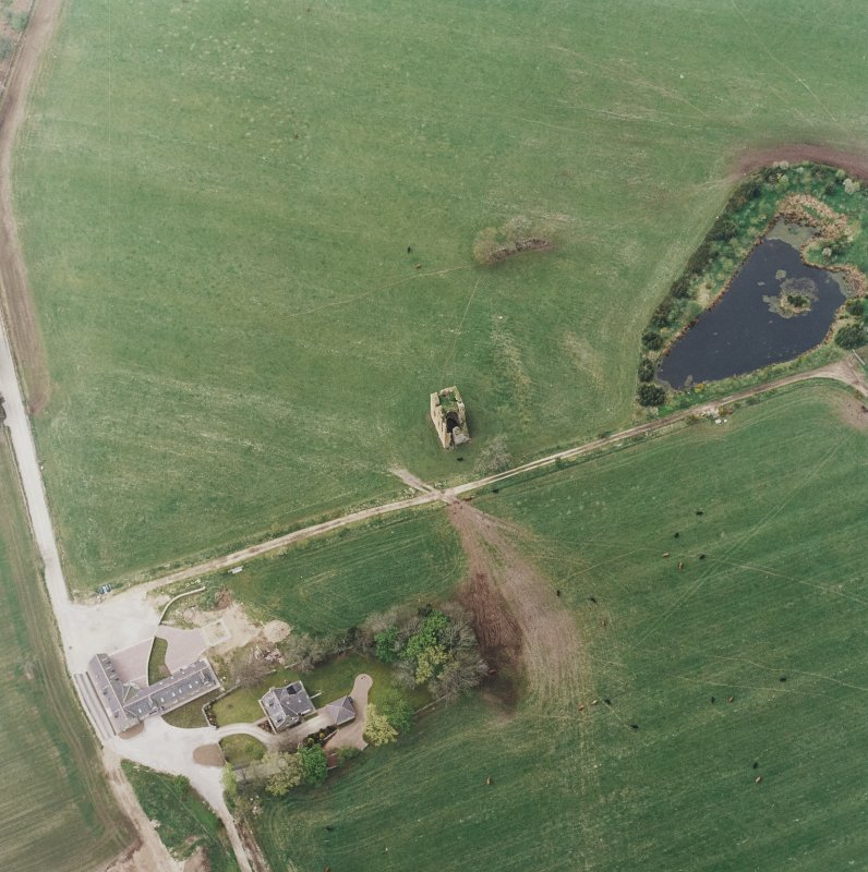 Oblique aerial view centred on the ruins of the tower-house with the farmsteading adjacent, taken from the ENE.