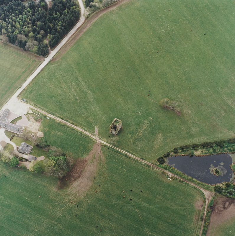 Oblique aerial view centred on the ruins of the tower-house with the farmsteading adjacent, taken from the NE.