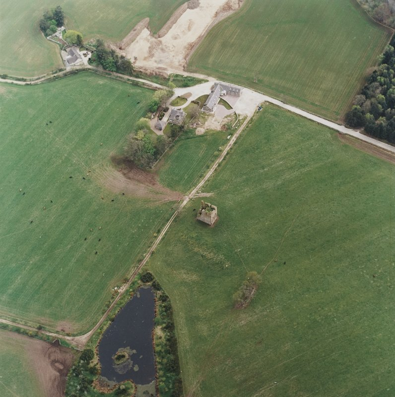 Oblique aerial view centred on the ruins of the tower-house with the farmsteading adjacent, taken from the NW.