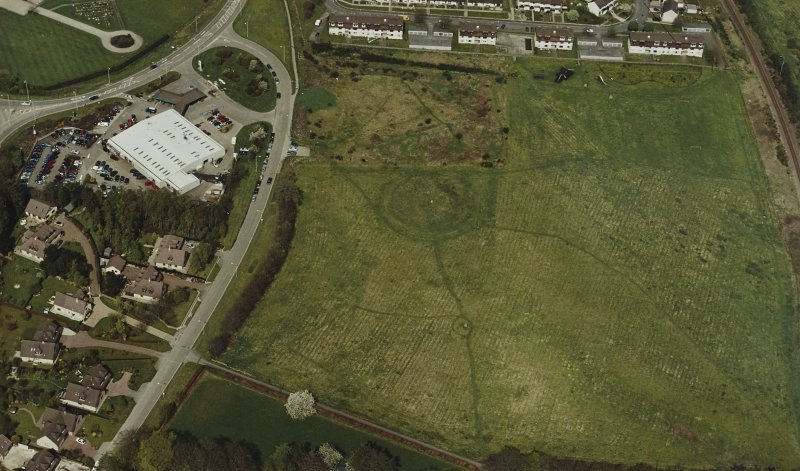 Oblique aerial view centred on the remains of the henge and stone circle, taken from the S.