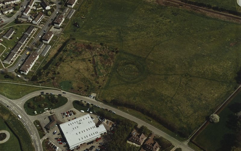 Oblique aerial view centred on the remains of the henge and stone circle, taken from the W.
