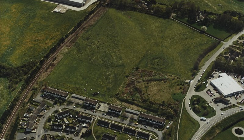 Oblique aerial view centred on the remains of the henge and stone circle, taken from the NNW.
