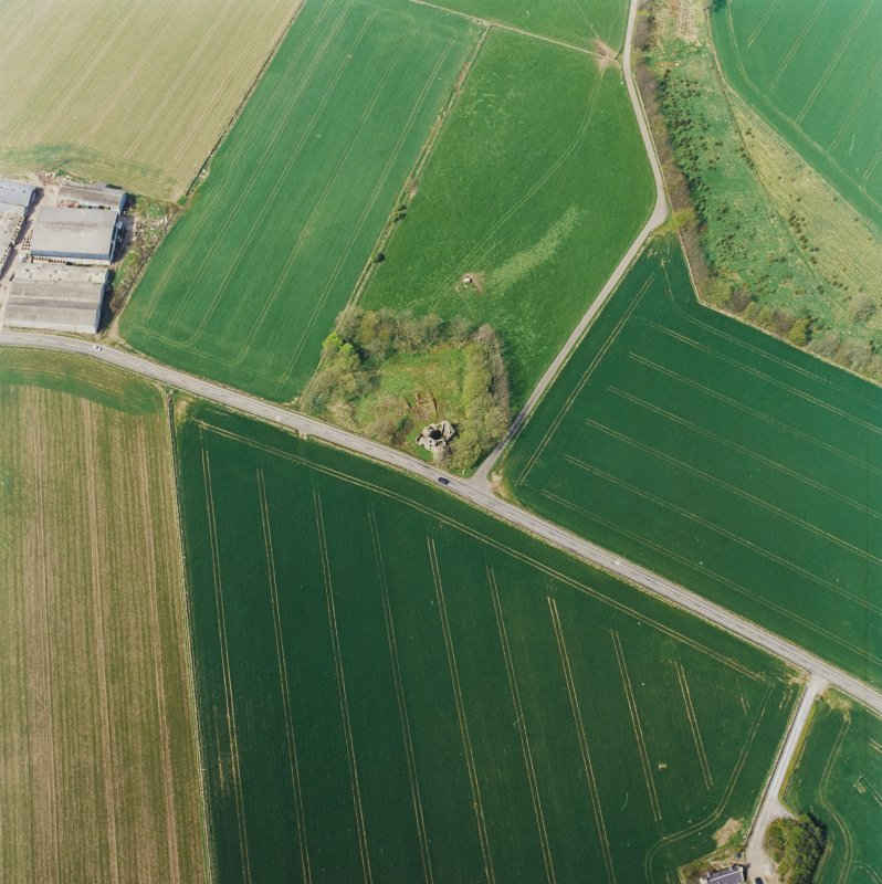 Oblique aerial view centred on the remains of the castle and tower-house, taken from the SE.