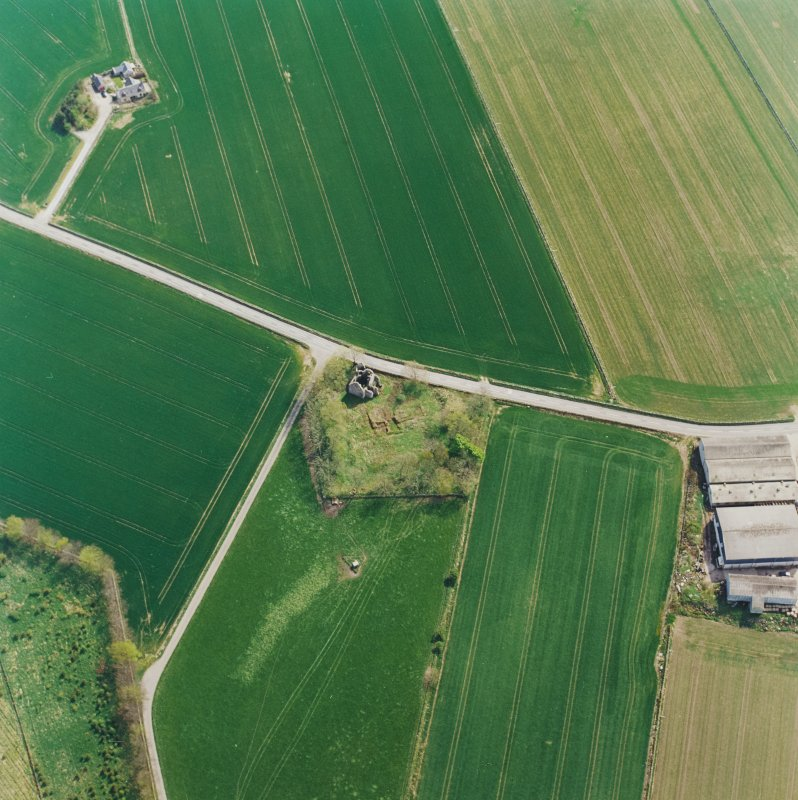 Oblique aerial view centred on the remains of the castle and tower-house, taken from the NW.