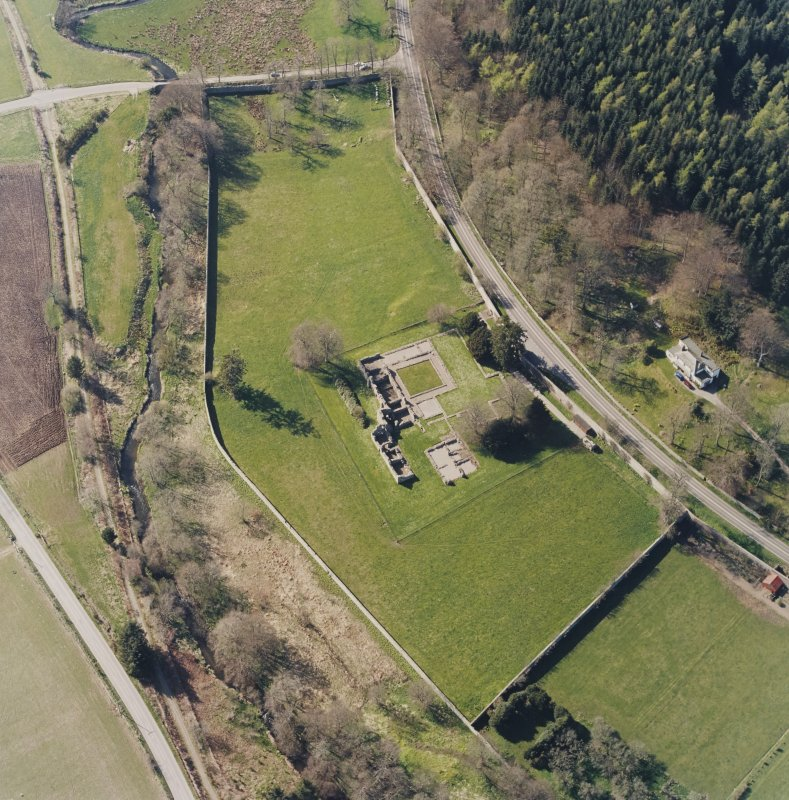 Oblique aerial view centred on the remains of the abbey and the house, taken from the ESE.