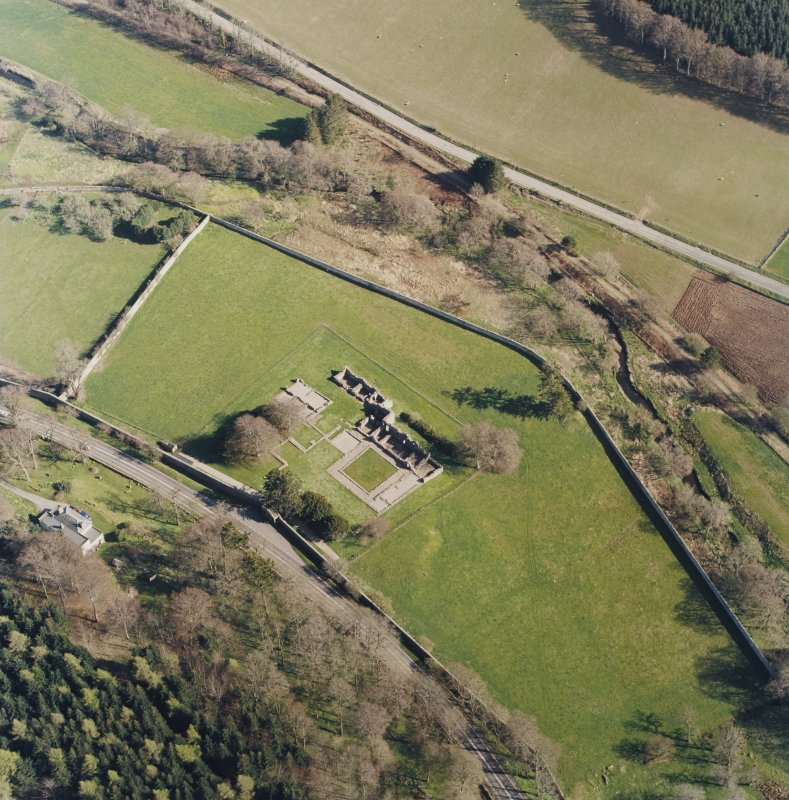 Oblique aerial view centred on the remains of the abbey and the house, taken from the NW.