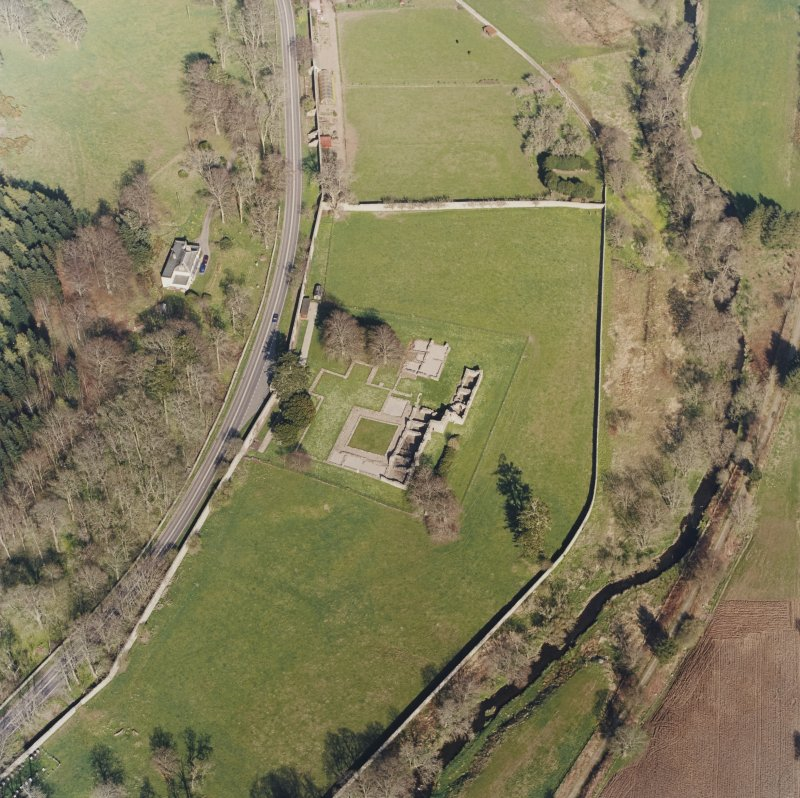 Oblique aerial view centred on the remains of the abbey and the house and walled garden, taken from the WSW.