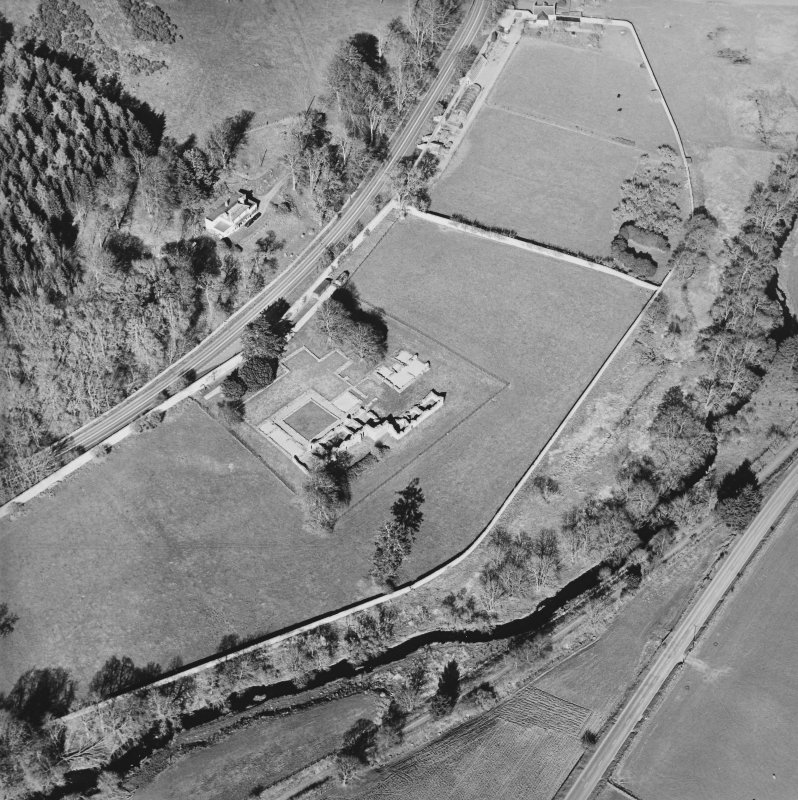 Oblique aerial view centred on the remains of the abbey and the house and walled garden, taken from the SW.