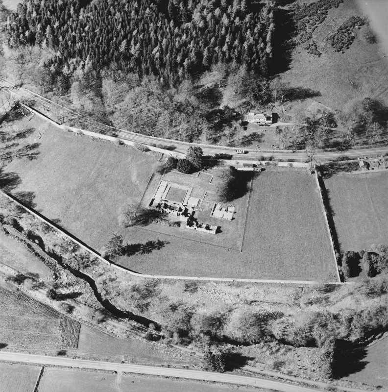 Oblique aerial view centred on the remains of the abbey and the house, taken from the S.