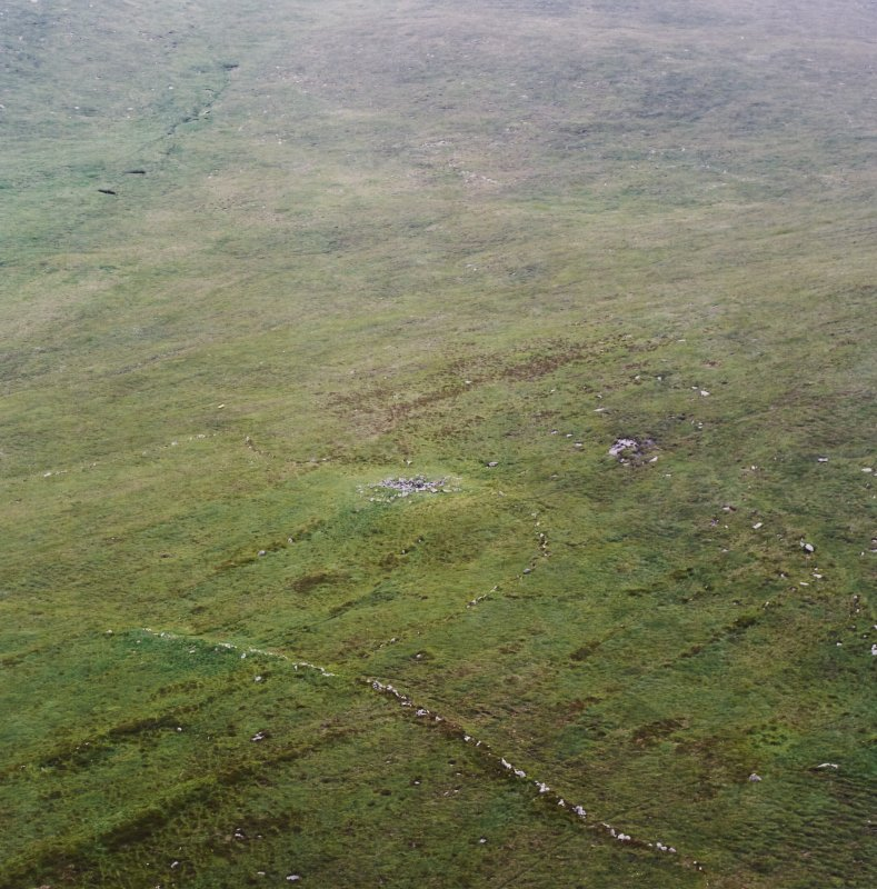 Oblique aerial view centred on the remains of the roundhouse with the field-system and lazy beds adjacent, taken from the SSE.