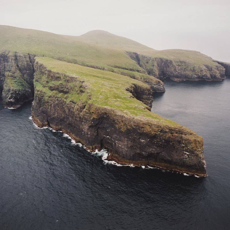 General oblique aerial view centred on the remains of the promontory fort, with coastal promontories and sea stacks adjacent, taken from the SW.