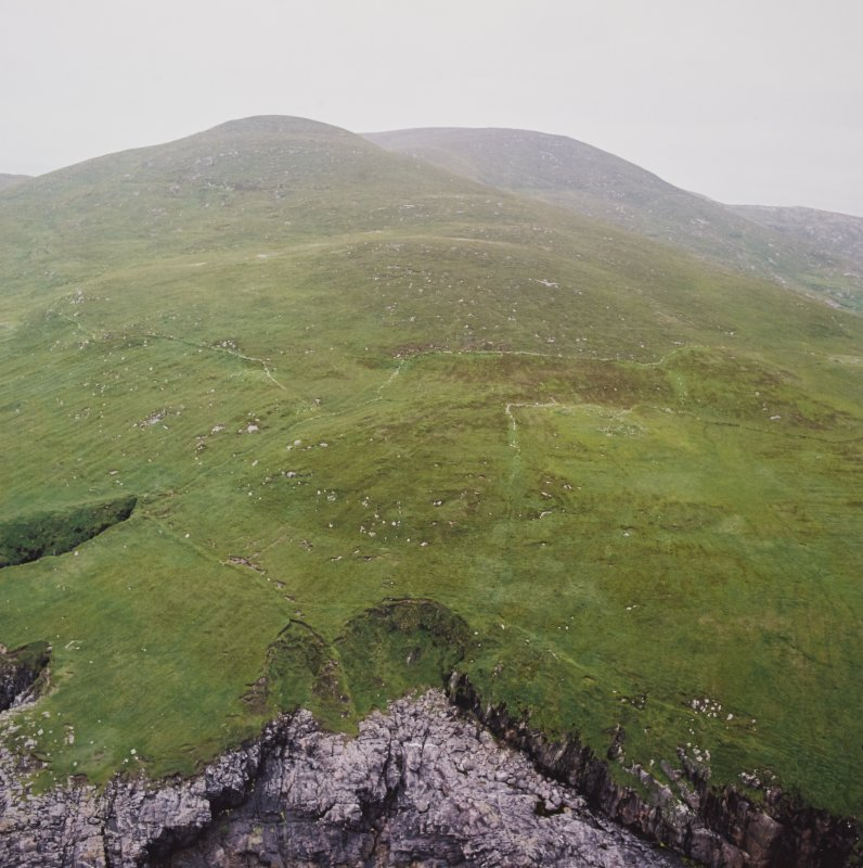 Oblique aerial view centred on the remains of a field system and buildings on the E slopes of Hecla on Mingulay, taken from the ESE.