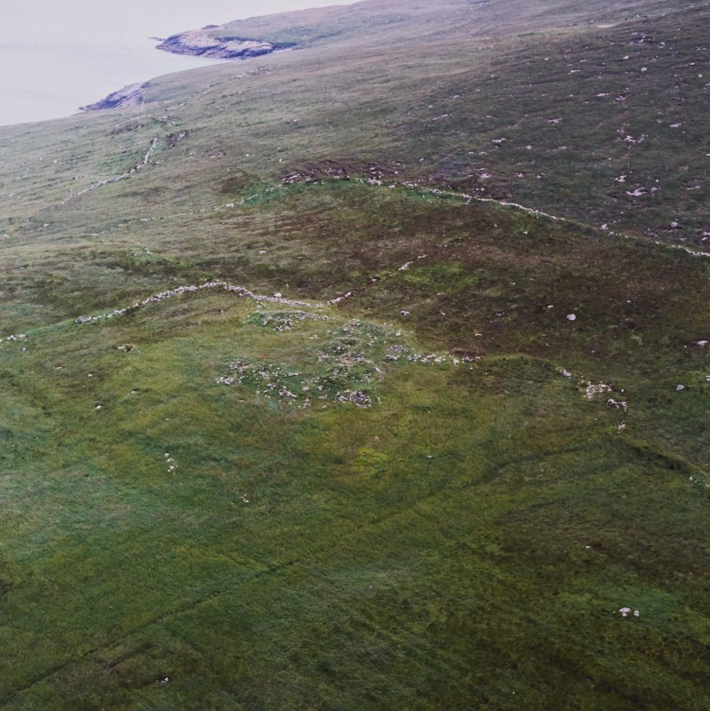 Oblique aerial view centred on the remains of buildings and settlement with the lazy beds and field banks adjacent, taken from the ENE.