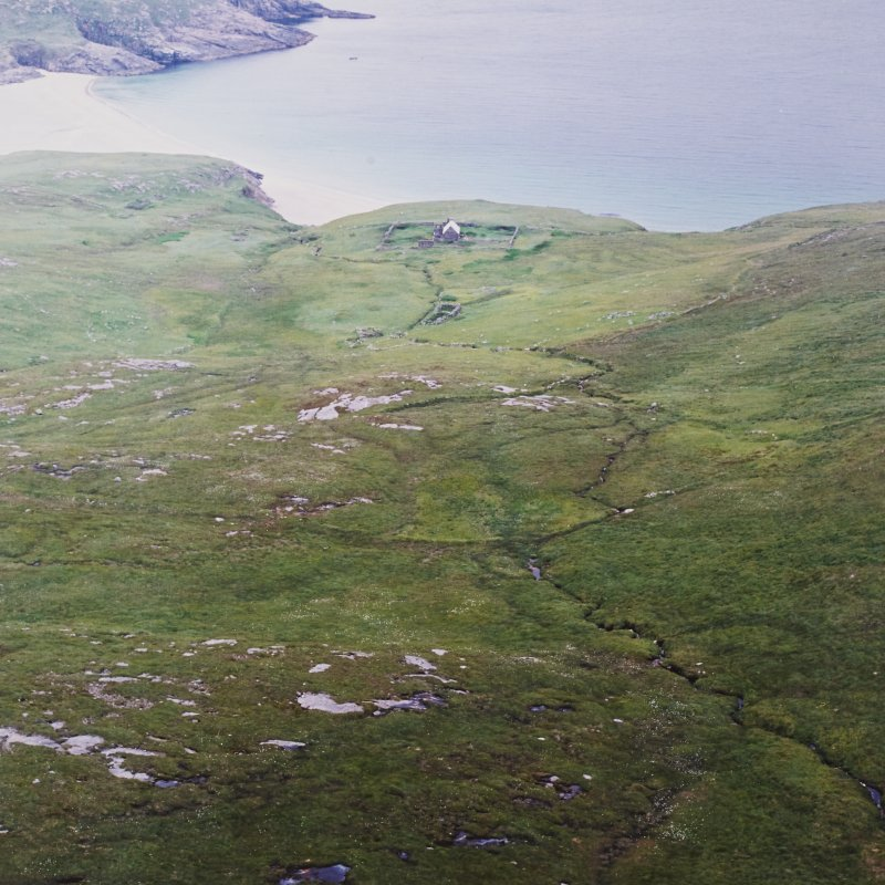 General oblique aerial view centred on the school and enclosure with the remains of the farmsteads and field-system adjacent, taken from the SW .