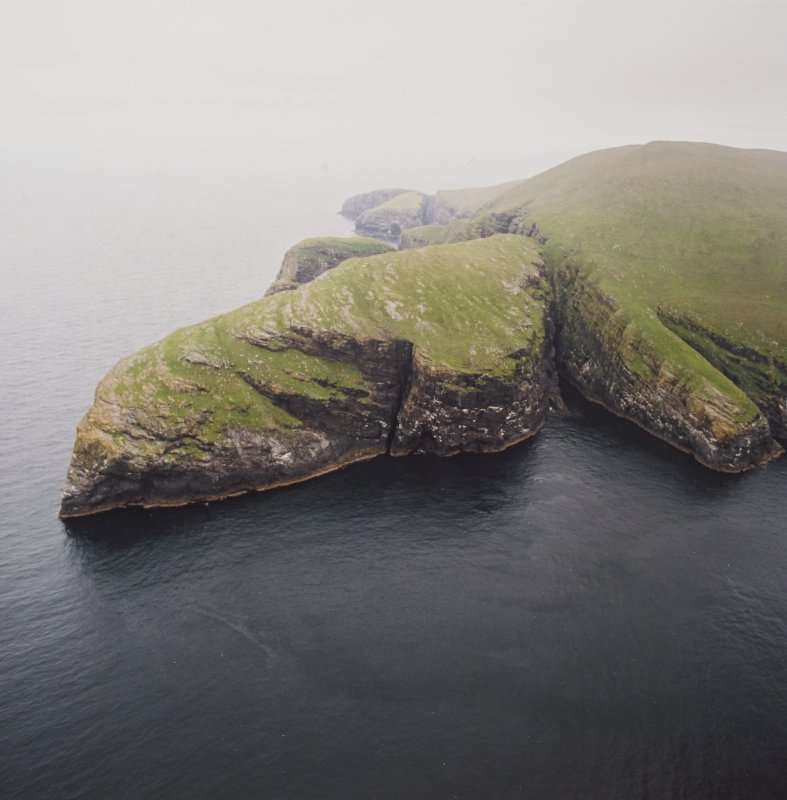 General oblique aerial view centred on the remains of the promontory fort, with coastal promontories and sea stacks adjacent, taken from the SSW.