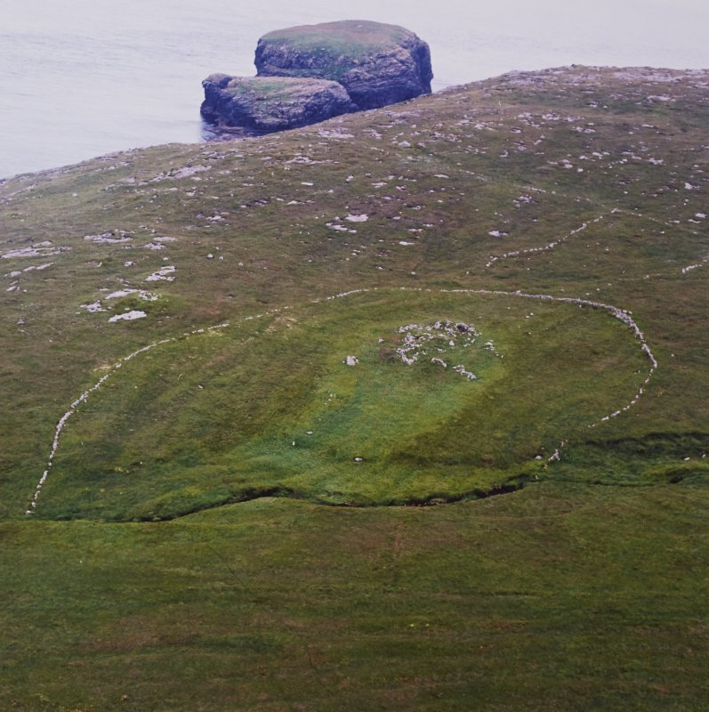 Oblique aerial view centred on the remains of the roundhouse, buildings, field banks and lazy beds, with the settlement mound adjacent and a peat stack stand in the foreground, taken from the NE.