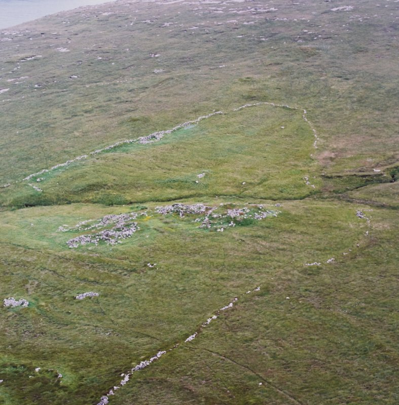 Oblique aerial view centred on the remains of the roundhouses and buildings with the enclosures and lazy beds adjacent, taken from the NE.