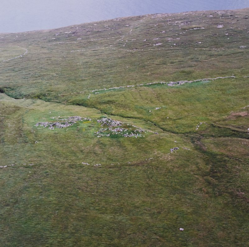 Oblique aerial view centred on the remains of the roundhouses and buildings with the enclosures and lazy beds adjacent, taken from the N.