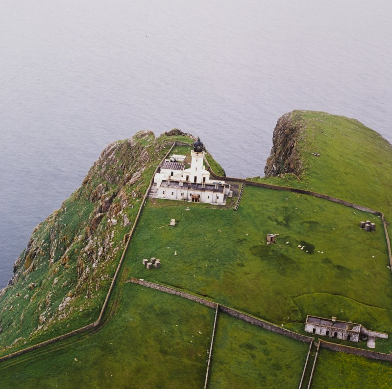 Oblique aerial view centred on the lighthouse with the remains of the dun adjacent, taken from the E.