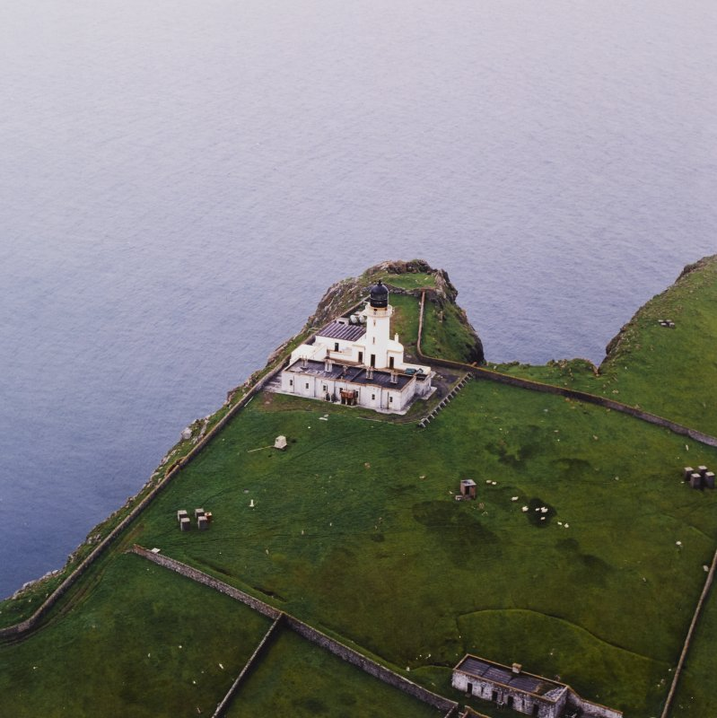 Oblique aerial view centred on the lighthouse with the remains of the dun adjacent, taken from the ENE.