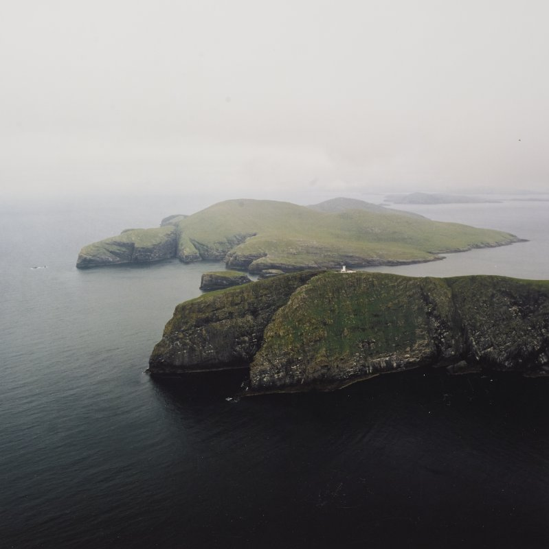General oblique aerial view of the lighthouse with the island of Mingulay and those to the N in the background, taken from the S.