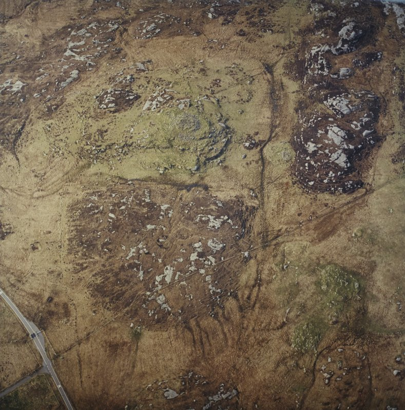 Oblique aerial view centred on the remains of the broch, taken from the NE.