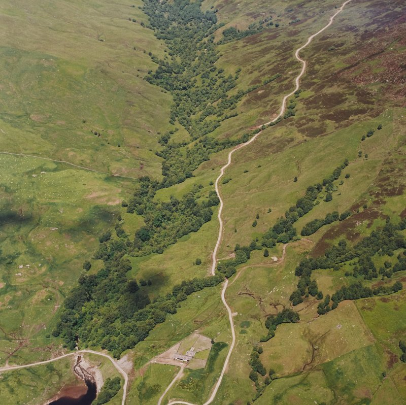 Oblique aerial view centred on the remains of field-systems, rig, head-dyke and shieling-huts, taken from the SW.