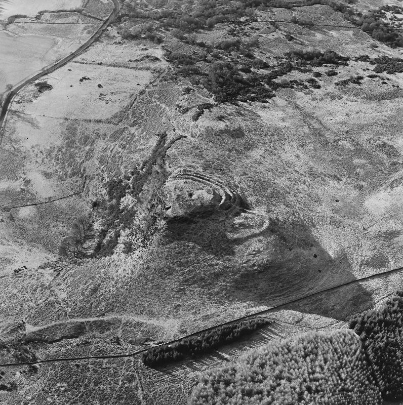 Oblique aerial view of Dunmore centred on the remains of a fort and well, taken from the NE.