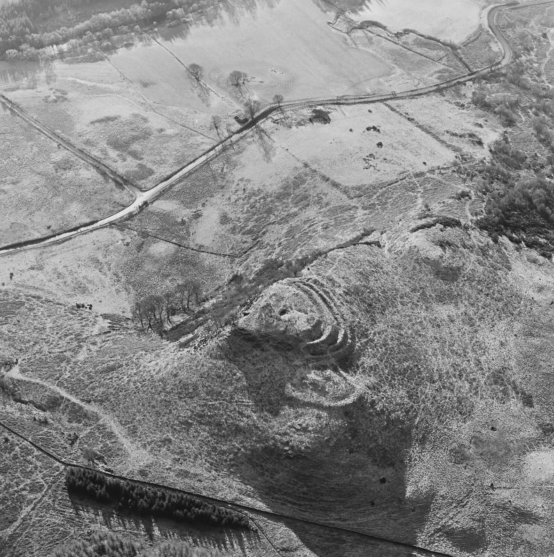 Oblique aerial view of Dunmore centred on the remains of a fort and well, taken from the N.