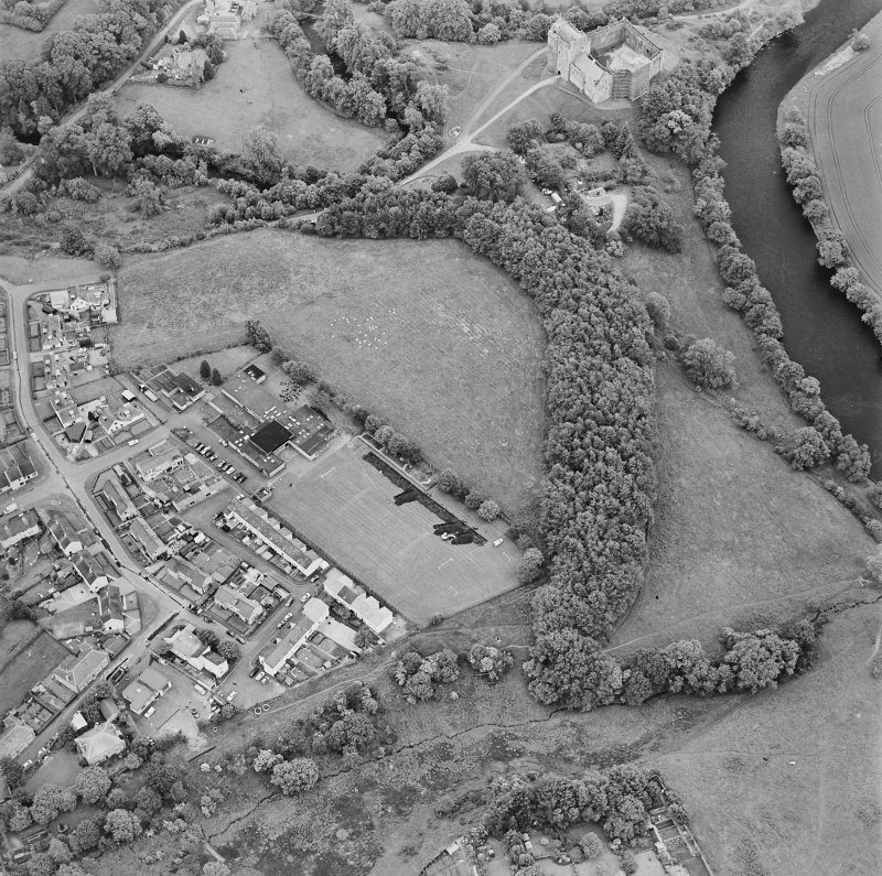 Oblique aerial view centred on the excavations of the Roman fort and possible annexe, with the adjacent castle, taken from the NW.