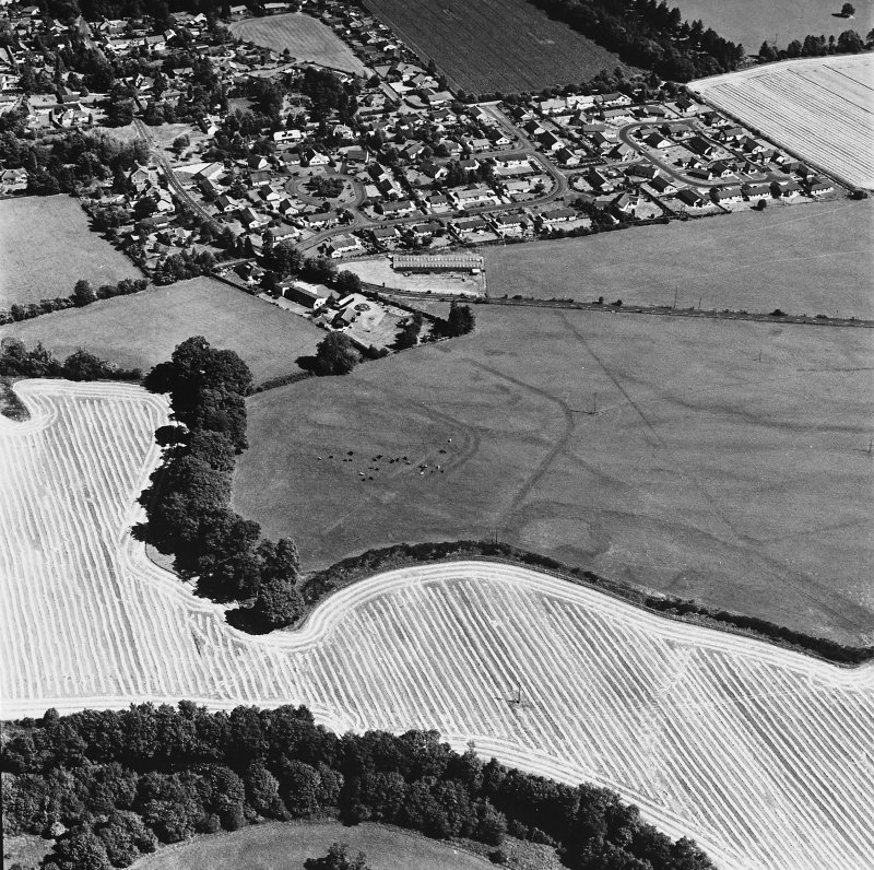 Dalginross, oblique aerial view, taken from the W, centred on the cropmarks of the Roman Fort. The Roman Temporary Camp is visible in the centre right of the photograph.