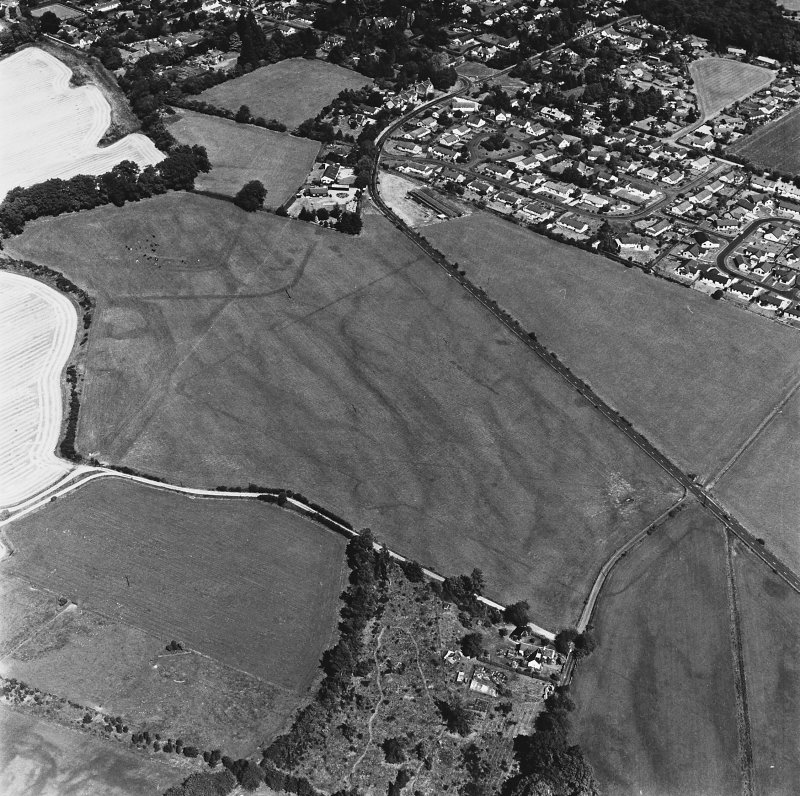 Dalginross, oblique aerial view, taken from the SSW, centred on the cropmarks of the Roman Temporary Camp. The Roman Fort is visible in the top left-hand corner of the photograph.