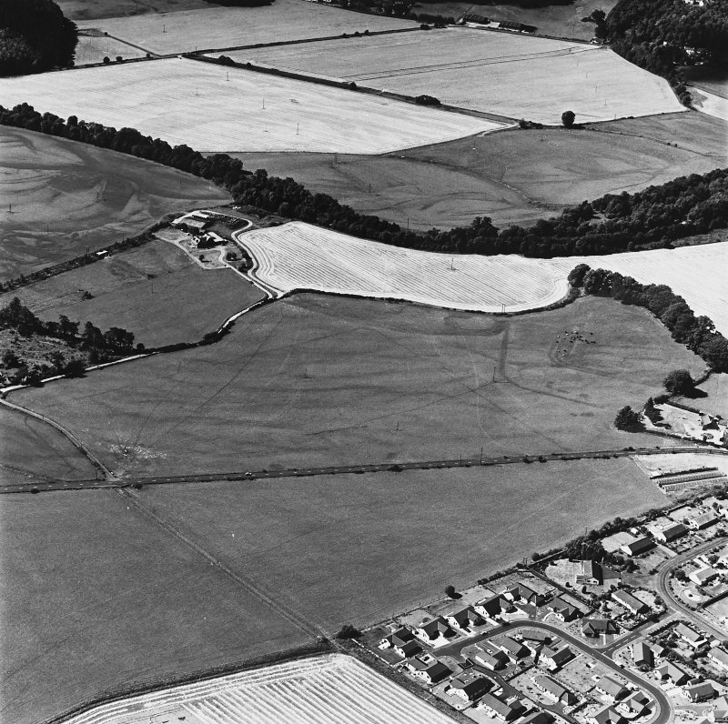 Dalginross, oblique aerial view, taken from the E, centred on the cropmarks of the Roman Temporary Camp. The Roman Fort is visible in the centre right of the photograph.
