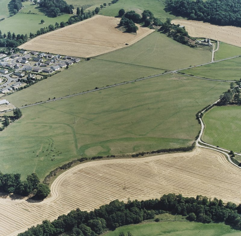 Dalginross, oblique aerial view, taken from the WNW, centred on the cropmarks of the Roman Fort and the Temporary Camp.
